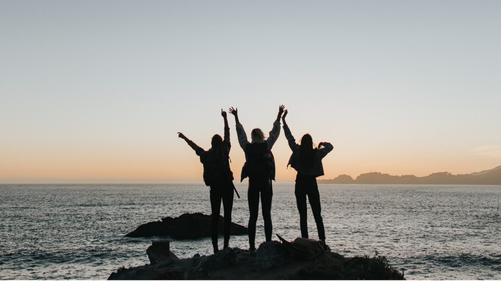 Women holding hands in front of the ocean