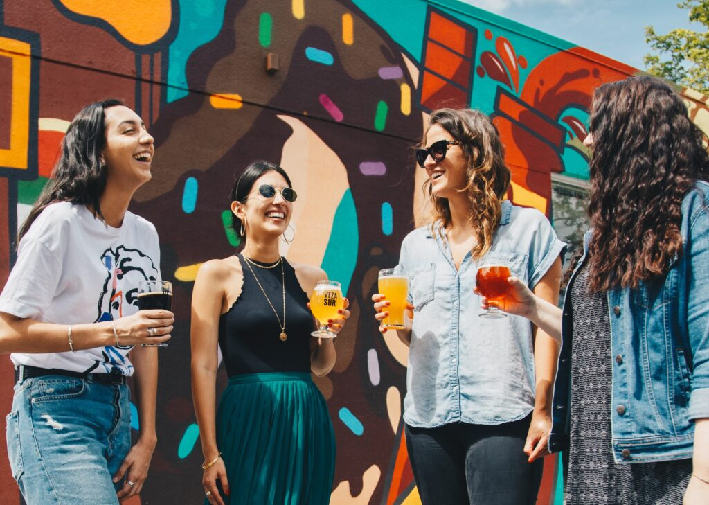 women chatting in a circle in front of a colourful wall